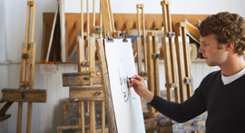 Man sketching on an easel.