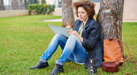 Woman drawing while sitting at base of a tree.